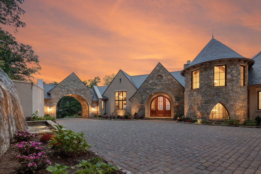 A beautiful home at dusk with stone facade, built by preferred builder Morgan-Keefe, located in The Cliffs at Walnut Cove.