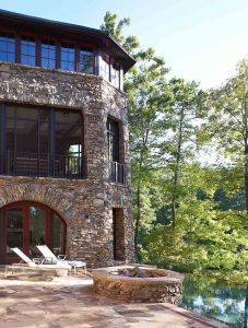 Tall stone home with fire pit and infinity pool.